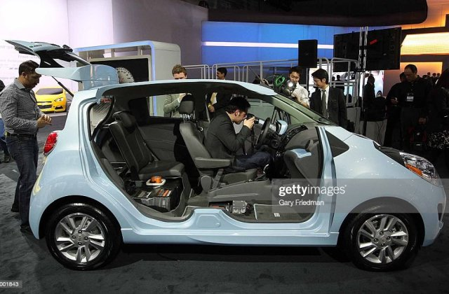 looking at the interior of chevrolet spark ev which photo - medium